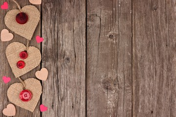 Side border of Valentines Day burlap hearts with buttons and confetti over a rustic wooden background
