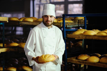 young handsome man baker in white uniform and cap on background bakery holding a loaf of bread