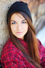 A pretty young blue-eyed brunette girl in a red tartan blouse and a black hat against a brick wall, closeup
