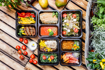 Healthy food and diet concept, restaurant dish delivery. Take away of fitness meal. Weight loss nutrition in foil boxes. Steamed veal with cous and vegetables at wood Wall mural