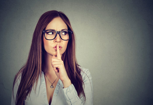 Woman saying hush be quiet with finger on lips gesture