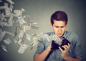 Sad man looking at wallet with money dollars flying away