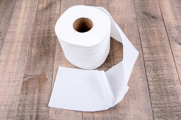 One roll of toilet paper isolated on a wood background