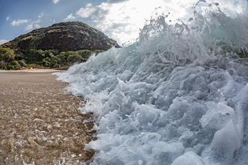 Shorebreak white foam. Wave crashing at sandy beach with droplets and splashes