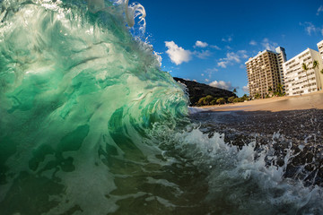 Big green wave crashing at shore near hotel at beach