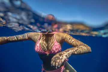 Girl underwater in blue ocean wearing pink bikini. Swimming sport action in vacation