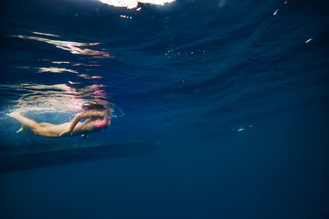 Girl in pink bikini underwater near bottom of a boat. Copy space on right side of image with blue water ocean background. Water surface with ripples above a model