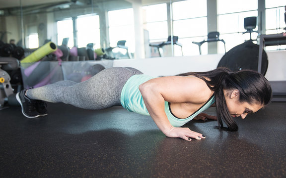 Strong, healthy woman doing push ups during gym workout