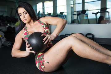Pretty girl working her core muscles with medicine ball during w