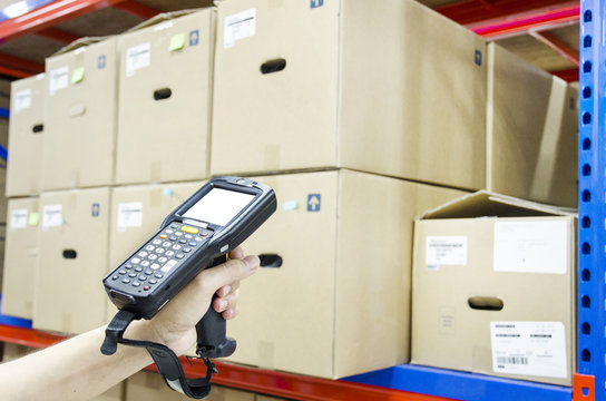 Hands holding portable barcode scanner in warehouse