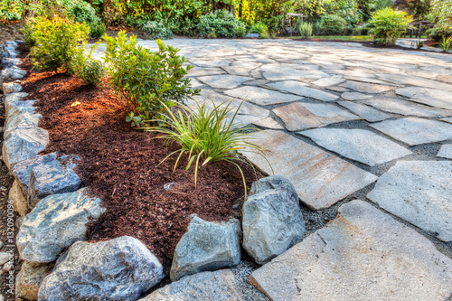 Fotobehang Completed flower beds around new stone patio with plants in place