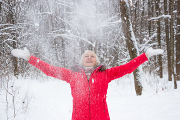 Portrait of a nice senior woman in the winter snow wood in red coat