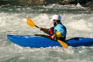 Side Profile of Extreme Kayaker Paddling in Raging River of White Water Rapids