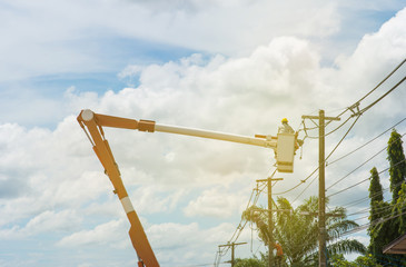 Electricians repairing wire of the power line on electric power pole on crane.