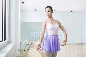 Young woman practicing ballet in dance studio
