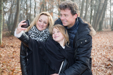 A family takes a picture with a smartphone in an autumn park