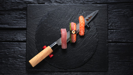Sushi served on japanese knife on a black slate plate