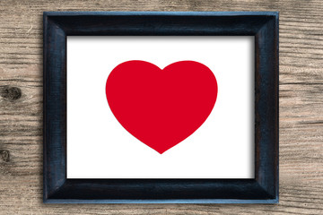 Red heart in photo frame on wooden background , valentine concep