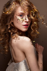 Beautiful girl in an evening dress and gold curls. Model in New Year's image with glitter and tinsel. Holiday picture. Christmas atmosphere.