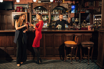Two attractive young women meeting up in a pub for glass of red wine sitting at counter smiling each other Wall mural