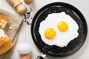 Fried eggs meal in a frying pan for delicious healthy breakfast. Traditional international breakfast food, top view.