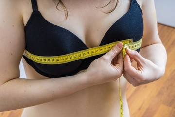 Young woman is measuring her breast size with a tape.