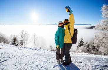 Skiers taking picture of themselves with smartphone over a mount