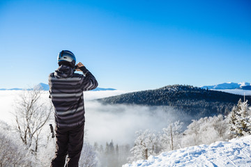 Man in winter clothes taking a selfie with mountains