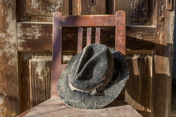 Battered old hat damaged by clothes moth on vintage background. A forgotten hat covered with spider web among the ruins of a house. Imagine the owner of this hat and tell their story.