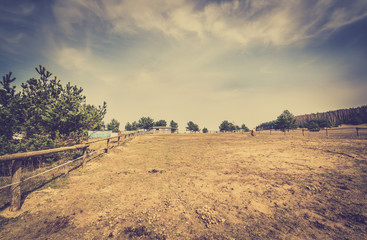 Landscape of ranch with dry grass and wooden fence