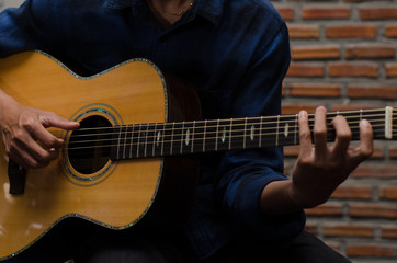 .A young man playing acoustic guitar happily in the music room.
