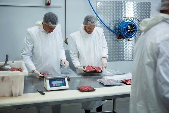 Butchers weighing packages of meat