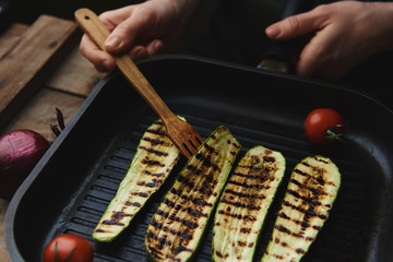 Woman cooking roasted vegetables on grill pan.