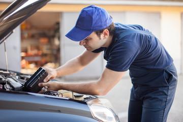 Car mechanic putting oil in a car engine