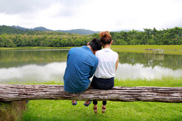 Young couple in love  sitting together on the timber near the lake with moutain and forest view