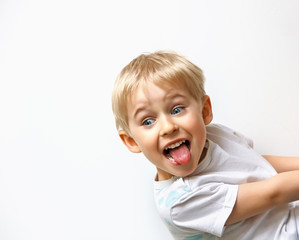 little boy teasing, showing tongue and makes a face, on white ba