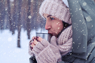 Concentrated woman holding a cup with a hot tea while looking at