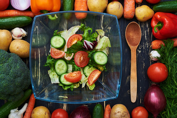 Fresh vegetable salad in a glass bow encircled in a frame made b