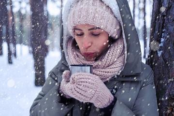 Pretty female blowing on tea while enjoying a mug of tea