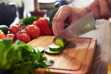 The procedure of slicing cucumber on a cutting board Wall mural
