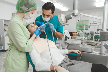 Dentist and nurse treating caries girl patient.