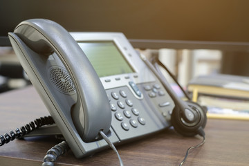 close up soft focus on telephone at office table desk with headset earphone:call center working job concept.