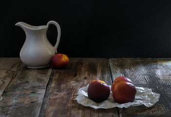White jug and peach on a wooden table