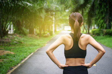 Back view of young fitness woman running on the road in the morning. People and sport concept, Sun light flare, Selective focus