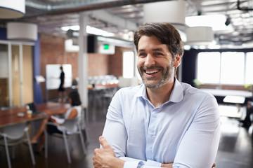 Businessman Standing In Modern Open Plan Office