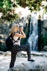 blonde girl photographer taking pictures at the waterfall