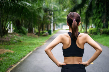 Back view of young fitness woman running on the road in the morning, People and sport concept, Selective focus