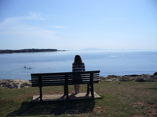 A girl sits on a bench and admire the Adriatic Sea. Beautiful morning.