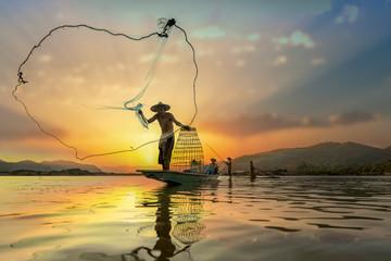 Asian Fishermen on boat fishing at lake