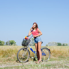 Young pinup woman cycling in fields under bright blue summer sky copy space image